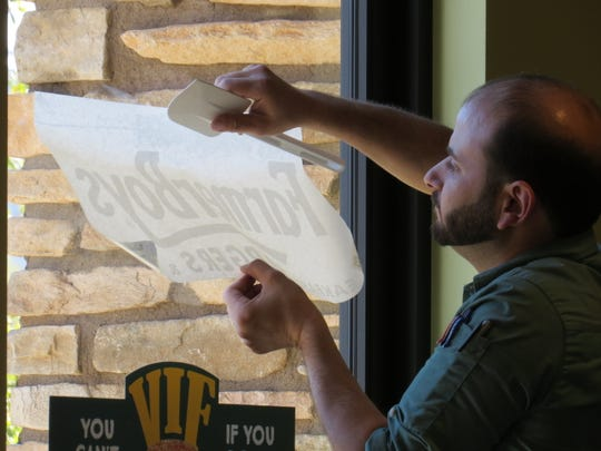 Rick Qaddur, general manager at Farmer Boys in Hollywood, applies a decal to the side door of the chain's new location in Newbury Park.