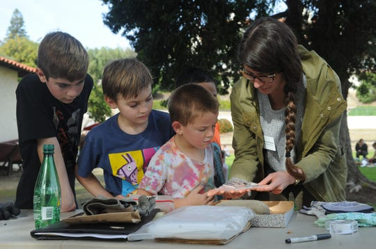 """(Left to right) Max Shrempf, 12, Julian Shrempf, 9, and Parker Lynn, 5, look at a shell with volunteer Briana Rotella on Friday, Jan. 24, 2020, at the Albinger Archaeological Museum in Ventura. The museum is celebrating its 40th anniversary with a weekend of events called """"Dig into History."""""""