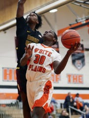 White Plains' Elijah Pierre (30) goes up for a shot in front of Mt. Vernon's Jovan Young (2) during boys basketball action at White Plains High School Jan. 23, 2020. White Plains won the game 67-66.
