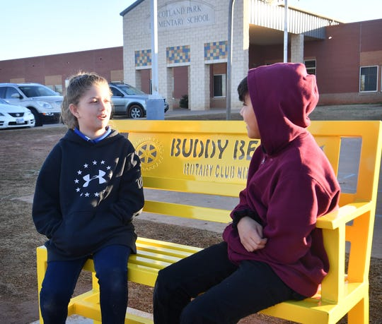 Audriana Busby and Jonathan Corona try out the new Buddy Bench intalled at Scotland Park Elementary School Friday. The bench was donated by the school's P.I.E. partner, Rotary Club North.