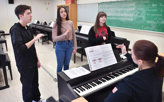 Rider High seniors Ashton Mastalsz, Angelica Concepcion and Rebekah Woodward, right, work with their choir teacher Melanie Coons. The students qualified for the Texas All-State Choir.