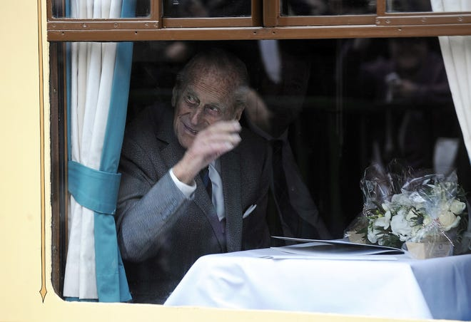 Prince Philip waves from inside the royal train carriage as the royal party prepare to leave Edinburgh's Waverley Station in Scotland in September 2015.