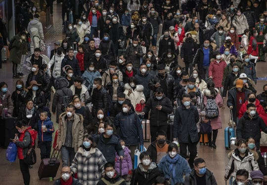 Chinese passengers, most wearing masks, arrive to board trains before the annual Spring Festival at a Beijing railway station on January 23, 2020 in Beijing, China. The number of cases of a deadly new coronavirus rose to over 500 in mainland China as health officials locked down the city of Wuhan in an effort to contain the spread of the pneumonia-like disease.