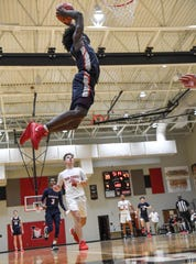Powdersville senior Draylan Burton(4) dunks near Liberty senior Levi Painter during the third quarter at Liberty High School in Liberty on Friday.