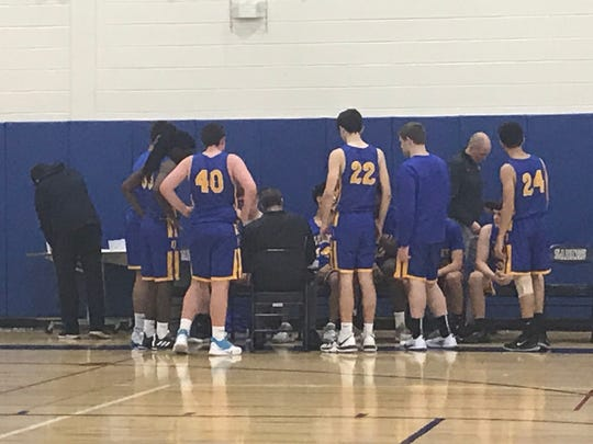 Oneonta High players gather around coach Jerry Mackey during a timeout in Friday's Southern Tier Athletic Conference game at Susquehanna Valley. The Yellowjackets won, 69-52.