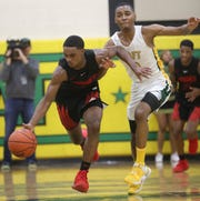 Hughes guard Kionte Thomas (5) brings the ball up the court against Taft guard Leroy Walker during they basketball game, Friday, Jan. 24, 2020.