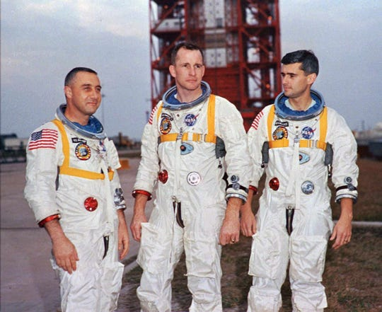 "Astronauts Virgil ""Gus"" Grissom, left, and Roger Chaffee, right, and University of Michigan grad Edward White II pose next to their Saturn 1 launch vehicle on Jan. 17, 1967."