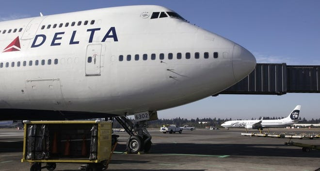 In this Oct. 9, 2012 file photo, Delta Air Lines 747-400 airplane sits parked at Seattle-Tacoma International Airport in Seattle. Delta Air Lines is being fined $50,000 for ordering Muslim passengers off planes even after the airline's own security officials cleared them to travel , Friday, Jan. 24, 2020. (AP Photo/Ted S. Warren, File)