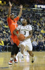 Michigan Wolverines guard Zavier Simpson (3) is defended by Illinois Fighting Illini guard Trent Frazier (1) during first half action Saturday, Jan. 25, 2020, at the Crisler Center in Ann Arbor.