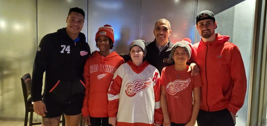 Detroit Red Wings players Madison Bowey, left, and Dylan Larkin, right, pose with Flint's Rico Phillips and three of his youth players at the Black Hockey History Mobile Museum on Jan. 18.