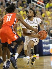 Michigan's Zavier Simpson drives against Illinois' Ayo Dosunmu during the second half Saturday, Jan. 25, 2020 at the Crisler Center.