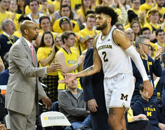 Michigan forward Isaiah Livers (2) slaps hands with assistant coach Saddi Washington as Livers exits the game after seeming to aggravate his groin injury in the second half.