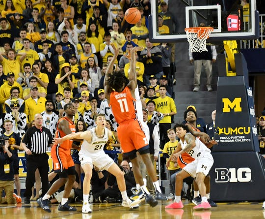 Michigan guard Zavier Simpson guards Illinois guard Ayo Dosunmu, who hits the winning shot for Illinois.