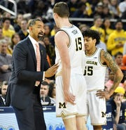 From left, Michigan head coach Juwan Howard talks with Jon Teske and Eli Brooks late in the second half.