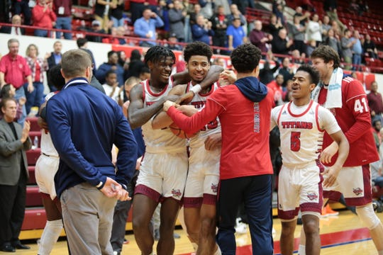 Alonde LeGrand is mobbed by teammates after hitting the winning shot for Detroit Mercy on Saturday.