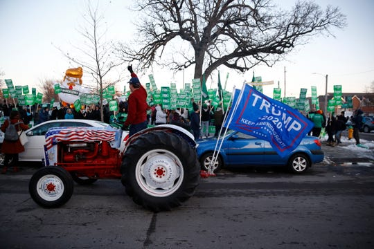 A President Donald Trump supporter rides by Democratic presidential candidate Sen. Amy Klobuchar, D-Minn., rally before a Democratic presidential primary debate Tuesday, Jan. 14, 2020, hosted by CNN and the Des Moines Register in Des Moines, Iowa.
