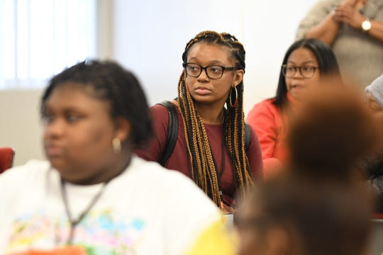 DayAnna Williams, center, listens to psychotherapist Marcia Phillips during The Who Am I conference in Southfield on Saturday, January 25, 2020.