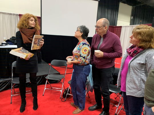 Designer Laurie Smith, left, signs and hands out copies of her interior design book to Caroline Kalvaitis, her husband, Tim Kalvaitis, and Marie Brown.
