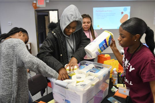 Niya Stone, left, Romiya Charleston, Natalie Brintlay, and Moriah Mixon fill a basket on Saturday, January 25, 2020, to be given to women at the Haven Center for Abused Women in Pontiac.