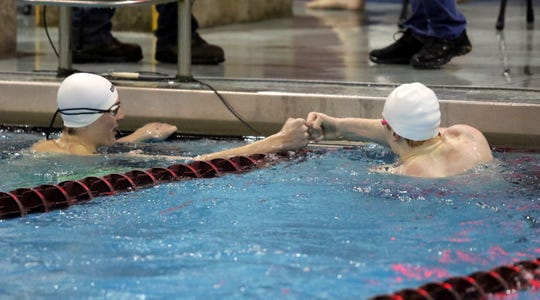 Chenango Valley's Eli Lanfear, left, and Corning's Ryan McNutt bump fists after the 100-yard freestyle at the John Beecher Boys Swimming and Diving Invitational at Ernie Davis Academy in Elmira on Jan. 25, 2020. Lanfear finished first and McNutt second, with both topping the state standard.