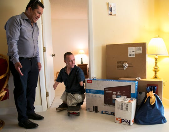 Dan Creighton, left, shows James Fox some of the gifts bought by community members during the reveal Fox's new condo on Friday, Jan. 24, 2020, in south Fort Myers.