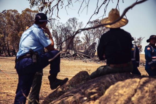 In this Friday, Jan. 24, 2020, photo provided by the New South Wales Police, police and other investigators stand in the shade of a tree near the crash site of a firefighting air tanker near Numeralla, south west of Sydney. Three crew from the U.S. were killed when their C-130 Hercules tanker crashed while fighting wildfires in Australia, their employer, Canada-based Coulson Aviation, said in a statement. (NSW Police via AP)