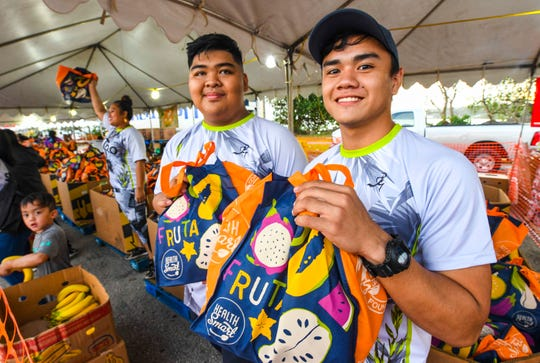 Pay-Less Markets employees, Jesmar Silvederio and Justin Santos, prepare to hand out goodie-filled reusable shopping bags to participants during Pay-Less Markets Community Foundation's 24th Annual Pay-Less Kick the Fat 5K/10K Run/Walk and Community Fair at the Paseo in Hagåtña on Saturday, Jan. 25, 2020.