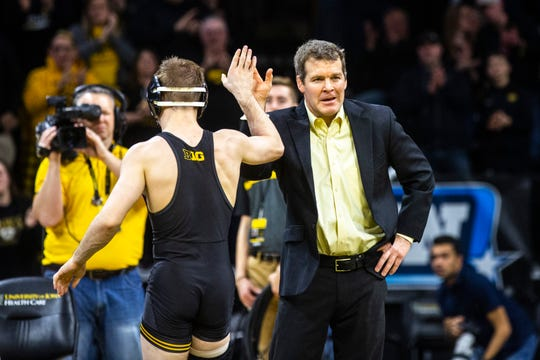 Iowa head coach Tom Brands, right, high-fives Spencer Lee after his match at 125 pounds during a NCAA Big Ten Conference wrestling dual against Ohio State, Friday, Jan. 24, 2020, at Carver-Hawkeye Arena in Iowa City, Iowa.