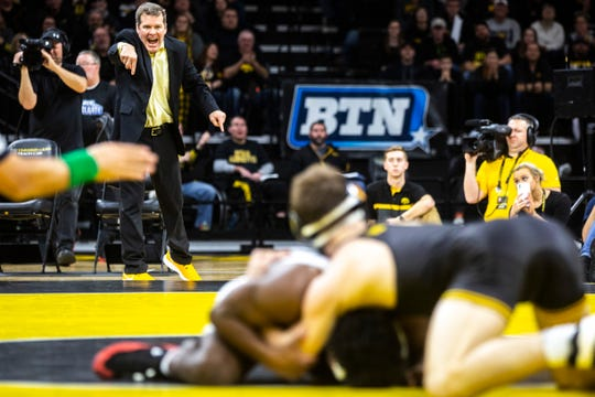 Iowa head coach Tom Brands gestures as Austin DeSanto, top, wrestles Ohio State's Jordan Decatur at 133 pounds during an NCAA Big Ten Conference wrestling dual on Jan. 24 at Carver-Hawkeye Arena in Iowa City.