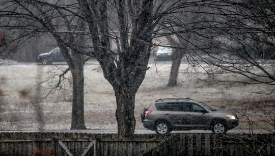 A morning commuter drives as snow flurries fall on the north side of Indianapolis, Saturday, Jan. 25, 2019