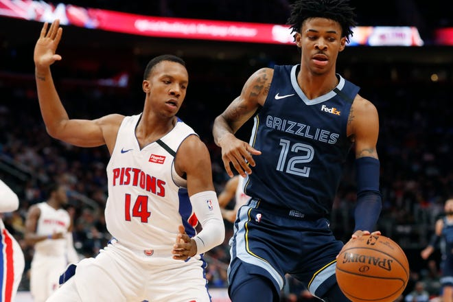 Memphis Grizzlies guard Ja Morant (12) controls the ball as Detroit Pistons forward Louis King (14) defends during the first half of their game Friday in Detroit.