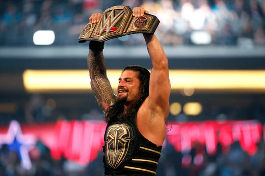 In this April 3, 2016, file photo, Roman Reigns holds up the championship belt after defeating Triple H during WrestleMania 32 at AT&T Stadium in Arlington, Texas.