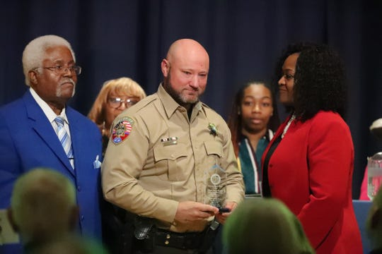 Rev. Goldy Wade, left, and Carolyn Cox, far right present Rutherford County School Resource Officer Shane Vaughn, center, a Jerry Anderson Hero award, during the NAACP's Martin Luther King Jr. Breakfast Celebration on Saturday, Jan. 25, 2020, at MTSU's James Union Building.