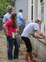 Volunteers from Acopia Home Loans work on the exterior of a Habitat for Humanity home.