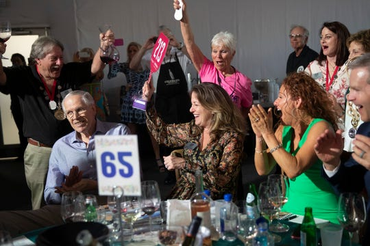 Kelley Jones celebrates after winning Lot 49 during the Naples Winter Wine Festival at the Ritz-Carlton Golf Resort in Naples on Saturday, Jan. 25, 2020,