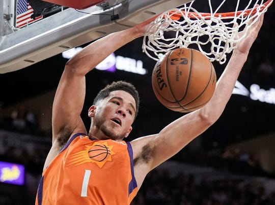 Phoenix Suns' Devin Booker dunks during the second half of an NBA basketball game against the San Antonio Spurs, Friday, Jan. 24, 2020, in San Antonio. (AP Photo/Darren Abate)