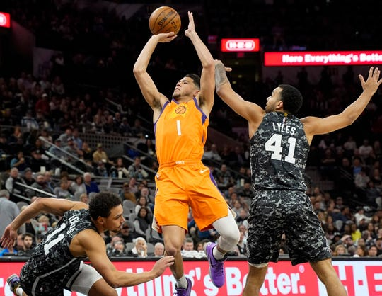 Jan 24, 2020; San Antonio, Texas, USA; Phoenix Suns guard Devin Booker (1) shoots against San Antonio Spurs guard Bryn Forbes (11) and forward Trey Lyles (41) in the first half  at AT&T Center. Mandatory Credit: Scott Wachter-USA TODAY Sports