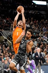 Jan 24, 2020; San Antonio, Texas, USA; Phoenix Suns guard Devin Booker (1) draws a shooting foul on San Antonio Spurs guard Bryn Forbes (11) in the first half  at AT&T Center. Mandatory Credit: Scott Wachter-USA TODAY Sports