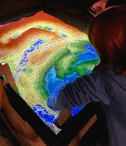 The augmented reality sandbox at the Schreder Planetarium lets users create topography models by shaping sand.