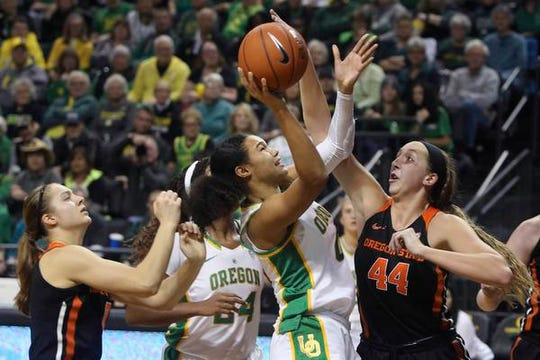 Oregon's Satou Sabally, center, shots between Oregon State, Mikayla Pivec, left, and Taylor Jones, right, during the fourth quarter of an NCAA college basketball game in Eugene, Ore., Friday, Jan. 24, 2020. (AP Photo/Chris Pietsch)