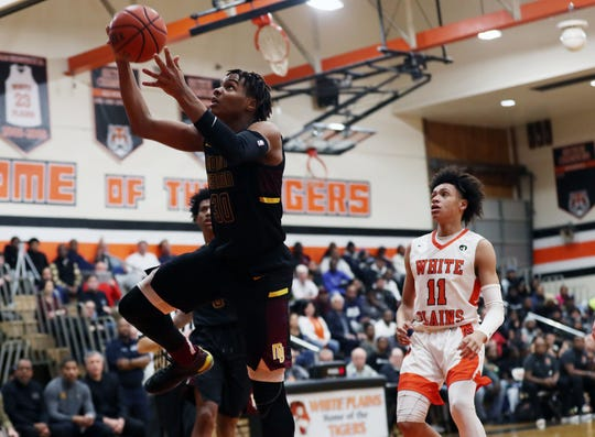 Mt. Vernon's Troy Hupstead (30) drives to the basket in front of White Plains' Tymir Greene (11) during boys basketball action at White Plains High School Jan. 23, 2020. White Plains won the game 67-66.