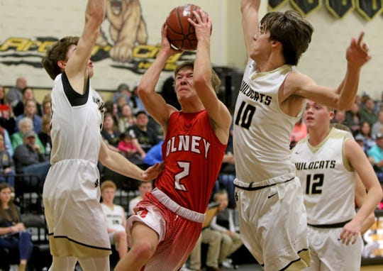 Olney's Carter Hinson drives to the basket between Archer City's Carter Hilbers, left, and Walter Kulhanek Friday, Jan. 24, 2020, in Archer City.