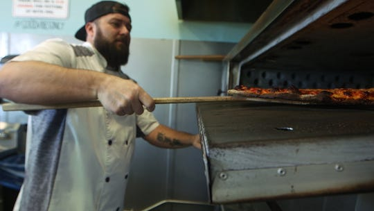 Owner and chef, Kris Black, pulls a hot pizza out of the over at The Galley Pizza & Eatery in Asbury Park