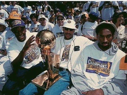 Left to right: John Celestand, Ron Harper and Kobe Bryant hold the Lakers' NBA Championship trophy in 2000.
