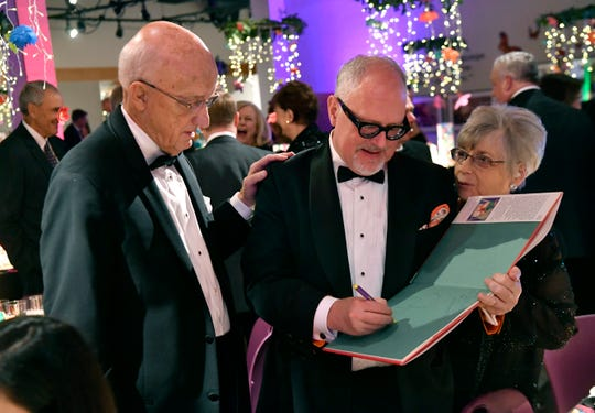 """Gary McCaleb rests a hand on the shoulder of William Joyce as he autographs a copy of his book """"Santa Calls"""" during Saturday's Storybook Ball."""