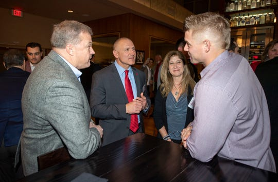 Head coach Steve Owens, second from left, talks with attendees during the Leadoff Banquet at The Rutgers Club on Saturday night.