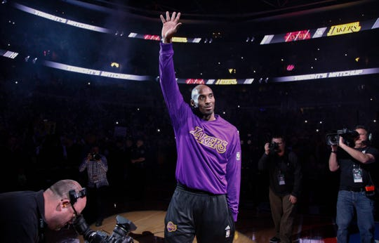 Kobe Bryant waves to fans before playing his final game against the Pistons on Dec. 6, 2015 at the Palace.