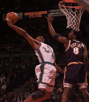 Pistons' Jerry Stackhouse flies to the basket against Lakers' Kobe Bryant, April 5, 1998 at the Palace of Auburn Hills.