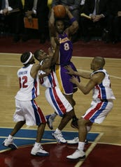 Kobe Bryant is defended by Richard Hamilton, left, Lindsey Hunter, center, and Corliss Williamson in the second quarter in Game 5 at the Palace.