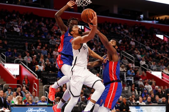 Spencer Dinwiddie drives on Detroit Pistons forward Sekou Doumbouya, left, and Andre Drummond in the first half Saturday.